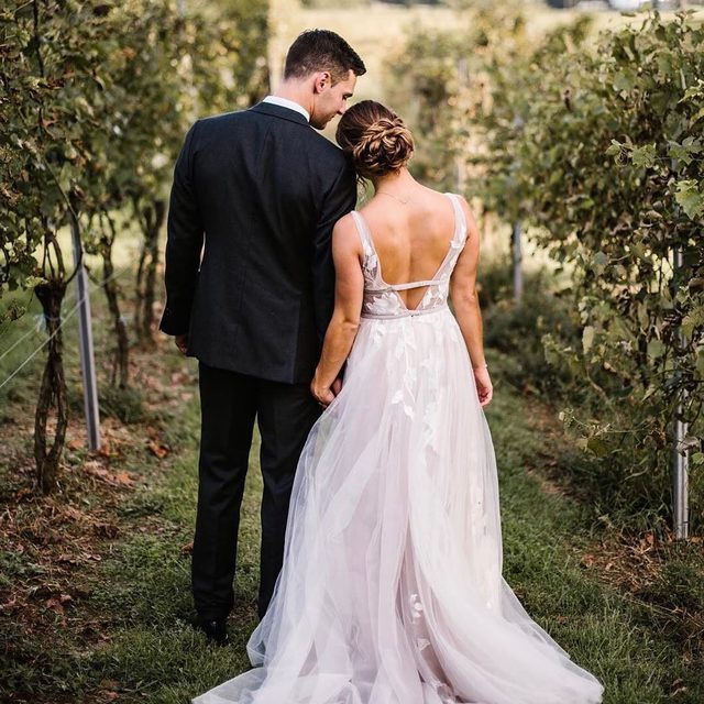 We kinda have a thing for vineyard weddings 💕 (tap to shop the Hearst Gown | 📸: @captured.by.alyssa)