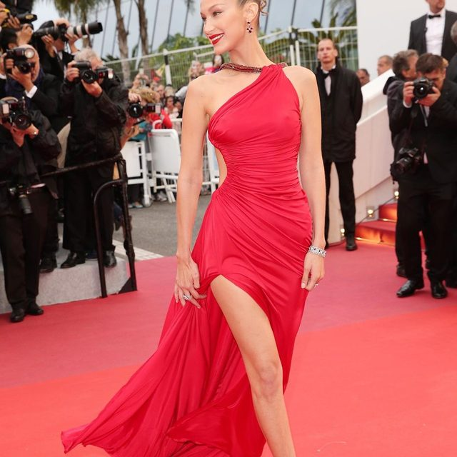 Lady in red! #BellaHadid looks incredible on the Cannes red carpet in a high leg slit gown—and just wait until you see the back. Link in bio. 💃🏻💃🏻💃🏻