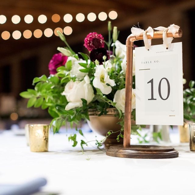 """Don't let any details go unnoticed on your big day. ✨ Until Tue 5/28, enjoy 15% off wedding and 25% off save the dates with code: MEMORIAL19. Tag future brides to let them know! @mintedweddings #linkinbio to shop. — """"Clean and Modern"""" foil-pressed table number by @kellyschmidtdesign. — Photo @davidstephen via bride @candidlykeri 