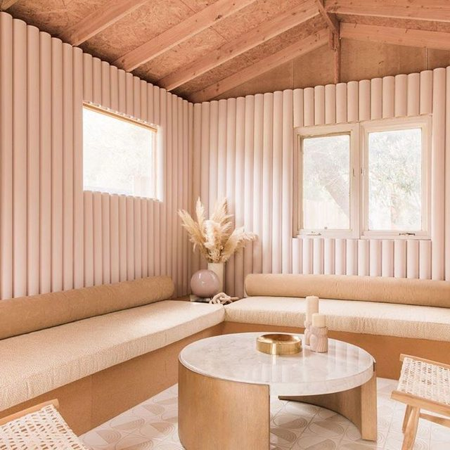 We love the look of a ribbed wall and Caroline Lee of @teamwoodnote let us in on how she DIYed them in her Palm Springs home: She had been seeing ribbed walls made from wooden dowels everywhere in Australia but the quotes she got from wood manufacturers were super high. So she called her friend, a skilled DIY-er, who talked her through fashioning the look from PVC pipes which they cut in half for the ribbed effect instead of wood💥For the built-in sofas, Caroline was originally inspired by Moroccan stucco but that shifted into a design using cork textile which is totally unexpected. See more of the space 👉 link in bio 📸 by @echoandearl