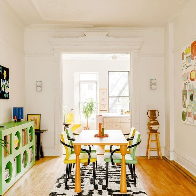"""@dusendusen's rule of thumb for decorating with bright colors? """"I never have the full rainbow,"""" she says. """"I never use every color of the spectrum"""" 🌈 Just take a look inside her BK apartment that's filled with Craigslist finds (that Sottsass dining table 🤯) DIY projects (those striped sconces 💡), and custom furniture from friends (that green bookcase by @sekeene 🍏). See more of the space 👉 link in bio 📸 by @maxb.photo ✍️ by @_h_mart_"""