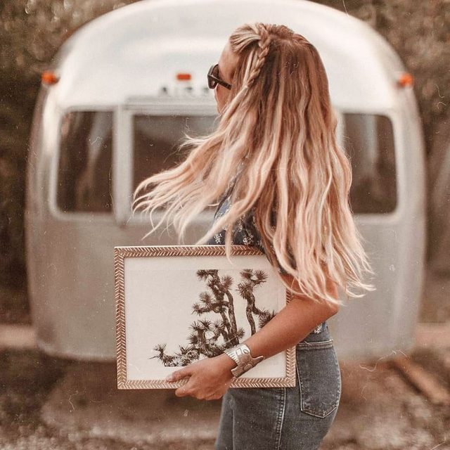"""Tiny living doesn't mean you should sacrifice style. Meet @mavistheairstream: adventurers who live and travel by Airstream.  #linkinbio to get their tips and tricks on how to decorate your RV with #MintedArt. — """"Joshua Tree in September"""" by @laroussephoto."""