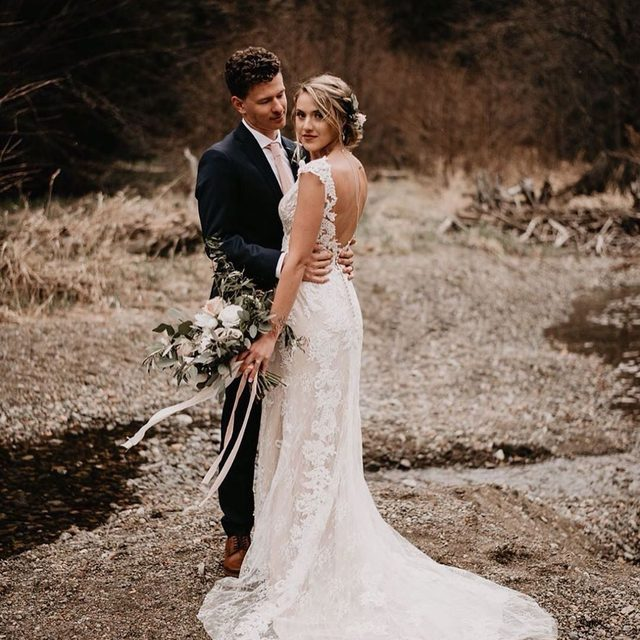 Our Milano Gown blends exquisite lace with delicate floral details. (tap to shop the look | 📷: @tayloraltonphoto 💏: @lily_c_gonzales + @claygonzales_ 💐: @mygardenoverfloweth)