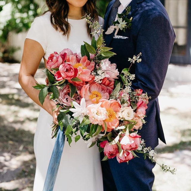 Peonies are one of the most requested wedding flowers of all time! 🌸 Can you guess the other 9? Head to the #linkinbio for the 10 most popular blooms! | 📸: @lukeandmallory 💐: sirenfloralco