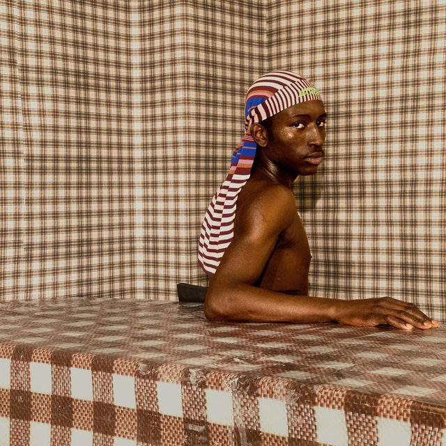 """In his series """"Haiti to Hood,"""" the 22-year-old photographer @daveedbaptiste charts the complicated birth of the Haitian-American identity. At first glance, the images seem like they could be documentary. In fact, they are heavily constructed—his elaborate sets are cluttered with objects that symbolize the activity of surviving under empire. See more at the link in our bio. Photographs by Daveed Baptiste."""
