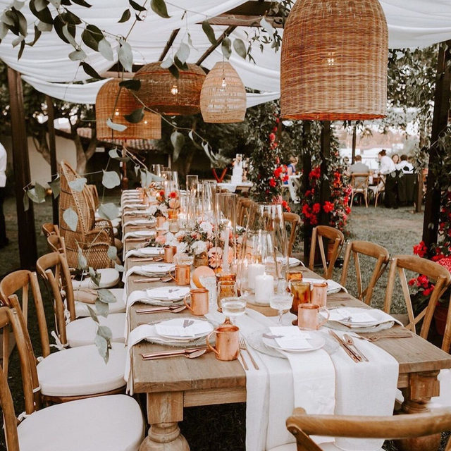 This couple transformed the same venue the bride's parents got married at into a ✨bohemian rhapsody.✨ Think: copper accents and pops of fuchsia, pampas grass and cacti, grapefruit centerpieces, and the coolest bridesmaid dresses ever. 🌺Head to the #linkinbio to see it all! #WeddingOfTheDay | 📸: @whitneydarling 📋: @roandcoevents 💐: @bloombabes