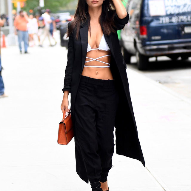 A bikini top, coat, trousers, and heels—that's how @emrata does summer-to-fall dressing. Tap the link in bio for the details on her look from the streets of NYC today. photo: splash news