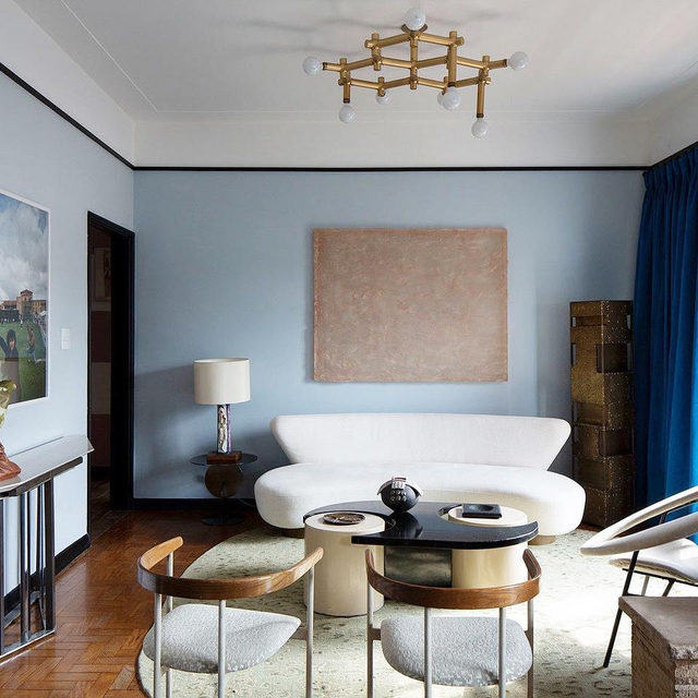 We love a good paint trick and this one is gold: designer @julianalimavasconcellos added a black frame around the living room of this São Paulo apartment to divide the icy blue wall color and white ceiling color *and* to give the impression that the ceiling is higher 😯 See more of the space 👉 link in bio 📸 by @andreklotz