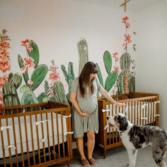 """Desert oasis nursery? 🌵 Sign us up! Blogger @kelseybang and her husband Jake recently welcomed home twin girls to this inspiring space featuring @susanmoyal's """"Cactus Fantasy Garden"""" wall mural design. #MintedMurals"""