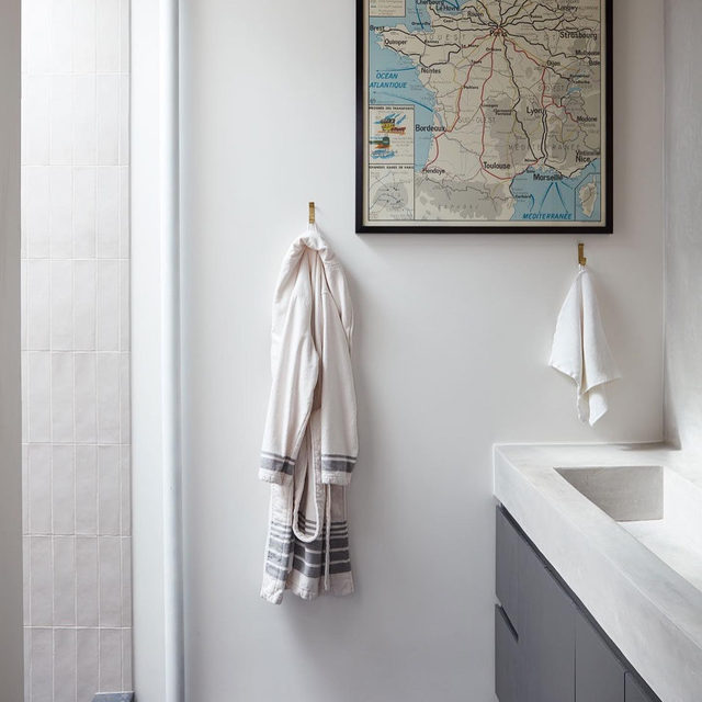 "What does one do with a small, cramped turquoise-tiled bathroom? (👉 for ""before"") Install a skylight 🌤 expand the footprint 📐 and finish it with serene tadelakt plaster walls for a spalike experience every day 🧖‍♂️ See more of @runnette and @nathanlump's Brooklyn apartment reno'd by @shapelessstudio 👉 link in bio 📸 by @david_a_land ✍️ by @my_shokoko; styled by @elizabeth.maclennan"