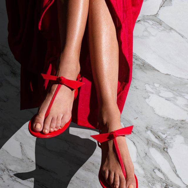 Standing out from the crowd in the red Jelly sandal. Discover available colors in alexandrebirman.com.br #AlexandreBirman #JellySandal
