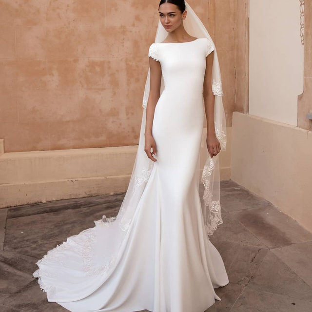 Stunning bateau neckline on the front and a breathtaking scoop back.  The Anitra dress is just perfect for the modern, elegant bride. Veil is V_2030CC #Pronovias2020 Book your appointment now!