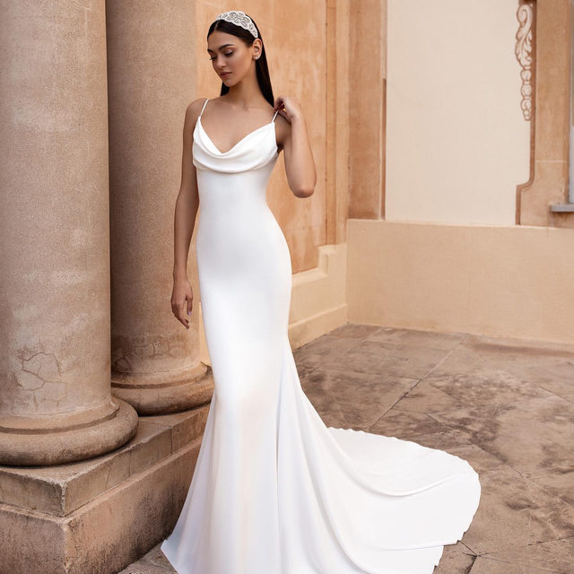 Antiope dress with the softest crepe and a sensual loose draping along the neckline 💫 Headband: Kindra. #Pronovias2020 Make an appointment to try it on.