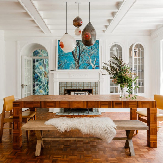 """When furnishing their family's 1918 NY home, @mollygfindlay and her husband Everard turned to friends and artists for unique pieces. The parquet dining table was made to fit the space by artist Gregory Rukavina, inspired by a conversation with their friend, sculptor Courtney Smith. The photograph on the mantel is by @cocodolle and the pendants are by the glass artist Melodie Beylik. """"Melodie lived with our family when I was little, and she is the most wonderful eccentric,"""" says Molly. """"She used to play 'Rock Lobster' and we would dance around on the rugs."""" Learn the stories behind their most special pieces 👉 link in bio 📸 by @maxb.photo"""