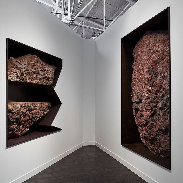 """#FOGFair: Gagosian is pleased to participate in FOG Design+Art 2020 with a presentation of works by Michael Heizer and Mary Weatherford. The fair opens today at the Fort Mason Festival Pavilion in San Francisco.  The booth features a pair of works from Heizer's ongoing """"Negative Wall Sculptures,"""" in which large rocks occupy steel-lined alcoves set into the walls of the booth, alongside Weatherford's highly atmospheric works on paper—some of the largest she has made to date.  Together, Heizer and Weatherford conjure a dialogue about our complex interaction with the environment at large. Heizer's unrefined rocks are contained by a smooth manmade alloy, yet they remain imposing—even seemingly impossible—in the apparent negation of their enormous weight. Weatherford's abstracted landscapes do not set urban and rural environments against one another, but immerse us instead in the artist's personal impressions of a world outside of time.  To receive a PDF with detailed information on the works, please contact the g"""
