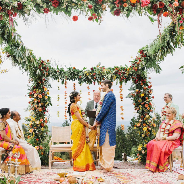 """This bride and groom transformed their wedding venue into the most colorful Indian celebration of love! 🌈 And to make sure all 250 guests understood every detail, they created a custom book that explained all the major traditions. For example, yellow is the color traditionally worn by brides with a Telugu background from South India 💛 and the process of showering each other with turmeric rice is called """"Talambralu"""" and symbolizes fertility, prosperity, and happiness! 😊 Head to the #linkinbio to see more of this floral-filled lakeside wedding! #WeddingOfTheDay 