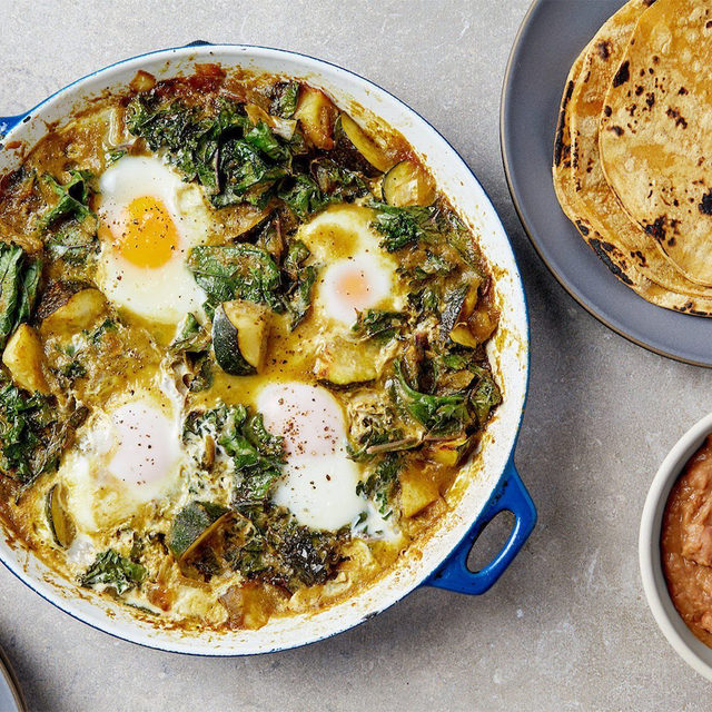 Our shakshuka–huevos rancheros hybrid uses green enchilada sauce instead of the more traditional red chili sauce. It's tangy, savory, and packed with veggies—and it comes together in about 20 minutes. #goopRecipe below:   Green Chili Eggs   1. In a 9-inch skillet, heat about 2 tablespoons of olive oil over medium heat. Add the onion and zucchini with a pinch of salt. After about 5 minutes, once they've softened a bit, add the green chilies. Let that mixture simmer together for another few minutes. Then add the green chili enchilada sauce and kale and cook for another 2 minutes or so.  2. Once the kale is just slightly wilted, make 4 small wells in the pan. Crack the eggs into the wells and cover the pan. Let the eggs cook for about 5 minutes, just until the whites are cooked through.  3. Serve with refried beans and warm corn tortillas.