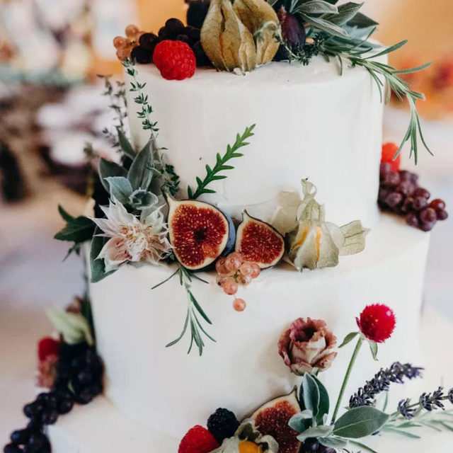 """The theme for this wedding was """"the power of love"""" and this cake is just one detail that shows it. 💖 Head to #linkinbio for a truly special wedding in Colorado that blended two families together in the trendiest of ways (think: custom Nike sneakers, a colorful wedding dress and one dreamy al fresco reception). #BridesRealWeddings 📸: @marymeckweddings 📋: @callunaevents 💐: @fawnsleap 🎂: @shamanesbakery"""