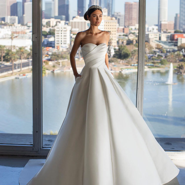 A draped, strapless bodice and flattering pleats falling from the waistline transform a simple A-line Mikado wedding dress into a vision of beauty. Accessorize with simple jewelry and a radiant smile. Meet Jurado! ✨ Un corpiño drapeado y sin tirantes en un precioso vestido mikado de silueta A. Compleméntalo con joyas sencillas y una gran sonrisa. ¡Descubre el vestido Jurado! ✨  @pronovias