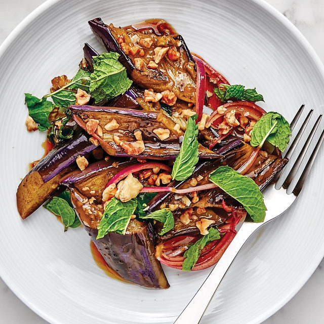 Whether you want a reason to buy those cool graffiti eggplants or you have a globe eggplant hanging around, this warm eggplant salad with walnuts is begging to be your dinner. It's savory, nutty, slightly sweet thanks to the addition of date syrup (or honey!), and is a very perfect vegetarian side or main dish. Click the link in our bio for @andybaraghani's recipe. 📷: @laurashoots 🍴: @susietheodorou