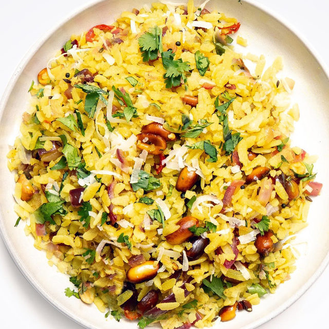 Poha, a staple in many Indian pantries, is rice that's parboiled, flattened, and dried. When grains of thick poha are hydrated, they become fluffy and absorbent, a quality that lends well to the eponymous hot breakfast dish popular in Western and Central India. And in writer Annada Rathi's house, kande pohe is what's for breakfast. Kande pohe is a savory, spicy, and cherished breakfast (or snack!) in Maharashtra in western India, with variations in many states. The dish consists of kande, which means onions in Marathi, and poha. The two are cooked together in the omnipresent tadka—spices that get fried in fat–along with peanuts, then garnished with grated coconut and chopped cilantro. Click the link in our bio to see how Annada makes it, and to learn about the cultural significance of kande pohe. 📷: @matt_tg