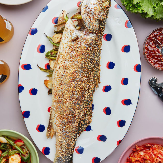 "In Korean, ssam literally means ""wrapped""—set this fish in the center of the table and pull the meat off the bones, using chopsticks to fill lettuce wraps along with radish salad, ssamjang, kimchi, and rice. @sohlae encourages you to try your hand at roasting a whole fish—it's low-maintenance and the flesh stays moist and flavorful even if you overcook it a touch! Plus, preheating your baking sheet will help prevent sticking, ensuring that nutty sesame seed crust keeps clinging tightly to the crisp skin. Click the link in our bio to get Sohla's whole fish ssam recipe. 📷: @emmafishman 🍴: @dbrownfoodstyle"