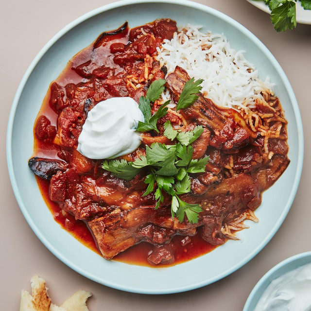 Khoresh bademjan, a Persian stew of spiced eggplant and tomatoes, is just the warming dish you need on a cool, fall night. It's typically made with lamb or beef, but @andybaraghani's version is faster and just as savory without meat. Don't forget to garnish with parsley and a dollop of yogurt. Click the link in our bio for the recipe. 📷: @emmafishman 🍴: @dbrownfoodstyle 🥣: @meilenceramics