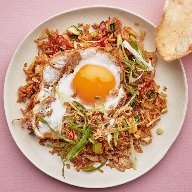 """It is no wonder that Indonesians eat nasi goreng for breakfast, lunch, and dinner,"" says Lara Lee (@laraleefood), the author of Coconut and Sambal: Recipes from My Indonesian Kitchen. Leftover rice is transformed into an umami-laden fried rice, topped with a crispy fried egg and a side of crunchy kerupuk, or savory prawn crackers. Named as one of Indonesia's national dishes and described by some as the world's greatest comfort food, nasi goreng is often seasoned with a combination of light soy, the fermented sweet soy sauce kecap manis, chilies, turmeric, and white pepper. Lee's version is a feast of texture and flavor, adding the fresh citrusy zing of the lemongrass and makrut lime to the sambal matah, a beloved condiment eaten all over the island of Bali. Click the link in our bio for Lara's vegetable nasi goreng recipe or watch her make it on our Instagram Story. 📷: @emmafishman 🍴: @rebeccajurkevich"