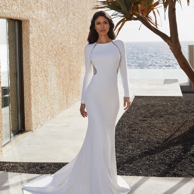 Ultra-fitted sleeves and a gorgeous peek-a-boo back with row buttons. Meet the Adela dress and try it on at your nearest #Pronovias store. Link in bio!