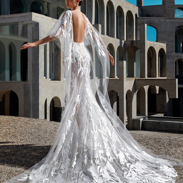 Make an statement in the flowing batwing sleeves framing a bare back of the Daniela gown from #AtelierPronovias New Premiere Collection. Book now your appointment. Link in bio. #Pronovias