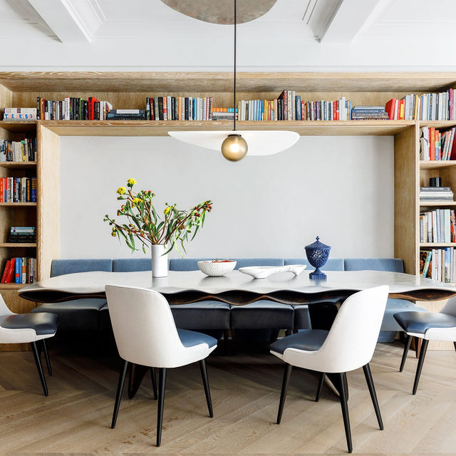 """In the dining room of a luxurious yet laid-back apartment in Manhattan's Carnegie Hill neighborhood, architect @mkcarchitecture's design ambition perfectly meshed with the family's needs. """"We wanted a room we could use every day for dinner,"""" the homeowner says, """"but one we could also occasionally glam up a little bit."""" To that end, Chen worked with @christopherkurtzstudio to design a table that is both indestructible and very, very glam: an aluminum surface with a rippled edge. For family meals, it stays pushed in toward the leather-and-mohair banquette. When they entertain, the table gets pulled into the center of the room and expanded with leaves cleverly hidden in a cupboard. The chandelier pivots so that the drop can be centered over the table in either spot. The vintage @osvaldoborsaniofficial chairs are from @nilufargallery, the custom chandelier is by @ladiesandgentlemenstudio, and the cabinetry is in cerused oak. Click the link in bio for the full tour as seen in our Jan/Feb 2021 issue. Written by @la"""