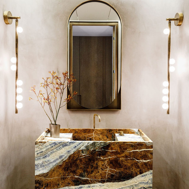 """In a Manhattan apartment designed by architect Michael K. Chen (@mkcarchitecture), the powder room has a vanity in Cassiopeia marble and a @vola.denmark faucet in lacquered brass. The custom mirror is by @kinandcompany, the sconces are by @lindseyadelman, and the walls are sheathed in Venetian plaster. """"We live in a city that is filled with artists and talent and creativity, and we wanted to harness that in our home,"""" says the homeowner, and this space is proof. Click the link in bio for the full tour, as seen in our Jan/Feb 2021 issue. Written by @langealexandra, photography by @maxb.photo."""
