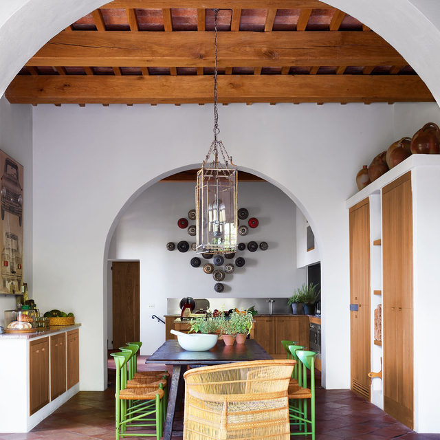 """This 16th-century Tuscan vacation house designed by @hubertzandberginteriors, which took two years to complete, was an exercise in balancing excess with restraint. While maximalism in the wrong hands can """"topple over into cacophony,"""" as the designer puts it, when executed with the scientific precision in which Zandberg specializes, it provides a mellifluous bounty. In the kitchen, the table is custom and the chairs are vintage. The woven chair is from Malawi, the pendant is from a Paris flea market, and vintage cake molds hang on the wall above the sink. Click the link in bio for the full tour as seen in our Jan/Feb 2021 issue. Click the link in bio to tour the rest of the home, which was featured in our Jan/Feb 2021 issue. Written by Nancy Hass, produced by @cynthiaefrank, photography by @simonuptonphotos."""