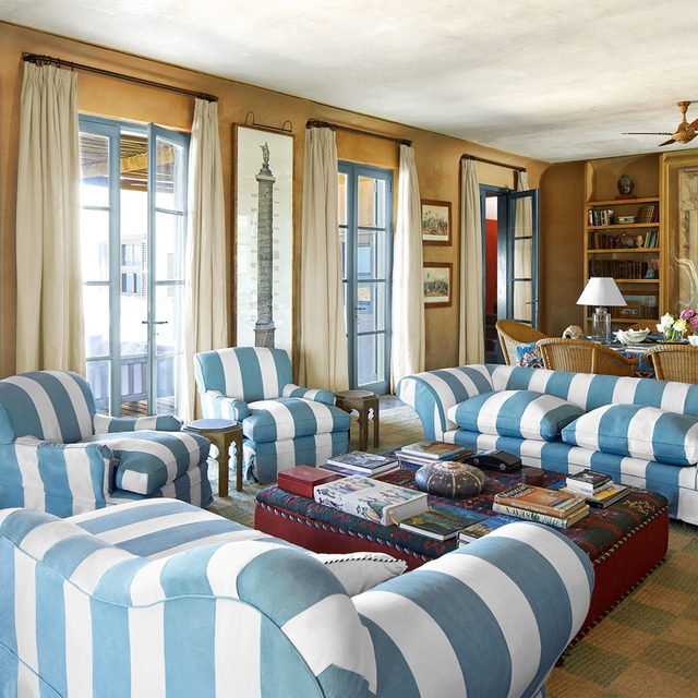 """""""It was so spectacularly beautiful, Mario's own house that he built for himself,"""" says the homeowner, who purchased the late architect Mario Connio's vacation home in Punta Piedras, Uruguay, and left the design mostly intact. The living room's eclectic decor consists of vintage pieces, curios procured from travels, and striking sofas upholstered in a bold pattern of white and seafoam green stripes—the architect's signature pattern. Made in England, the distinctive """"Connio stripe"""" had been discontinued, but the couple convinced the manufacturer to run the pattern again, so they could reupholster. The pink stucco wall finish was matched by the architect to a bottle of sand from Petra in Jordan. Click the link in bio for the full tour as seen in our Jan/Feb 2021 issue. Written by @karinaztn, produced by @dmmaciver, photography by @ricardolabougle."""
