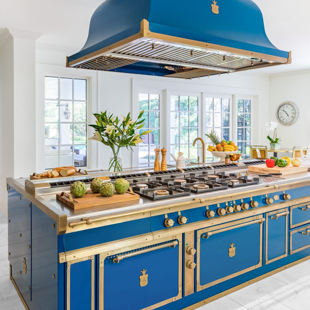 An ocean-blue island with burnished brass trim, handcrafted in Italy by @officine_gullo, creates a striking focal point in this crisp white kitchen. The design is timeless in itself, but the appliance is a home chef's dream for many reasons. This kitchen staple checks off all the boxes: A professional double oven, six burners, a pasta cooker, stainless-steel surfaces, and more. Feeling inspired? Head to the link in bio to explore the options for yourself—all of which can be fully customized, from general configurations to engraved drawer handles.