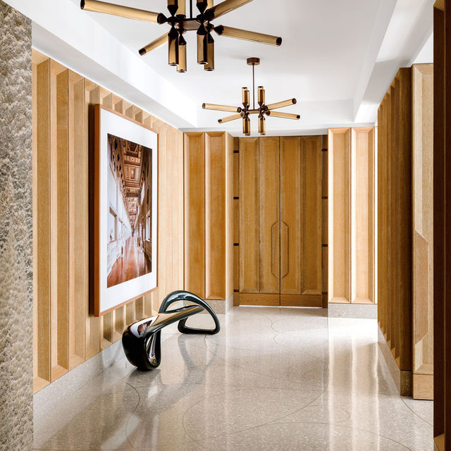 Architect Michael K. Chen (@mkcarchitecture) removed most of the walls from this Manhattan apartment—features that were put up during 1980s renovation—and in turn created a fluid floor plan. The private elevator opens into a cerused oak–paneled gallery—floored in hard-wearing terrazzo—that feeds visitors into the living room, dining room, and den through salon-style doors. In the gallery, a @candidahoefer_official photograph hangs above a lacquered fiberglass bench by @brodieneill, and the pendants are by  @jasonmillerstudio for @rollandhill. Click the link in bio for the full tour as seen in our Jan/Feb 2021 issue. Written by @langealexandra, photography by @maxb.photo.