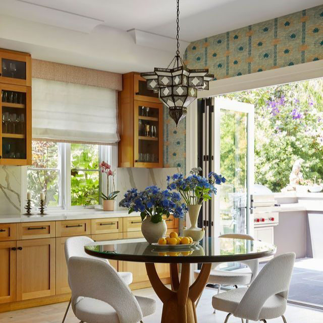 Opposites attract in this Santa Monica home designed by @natashabaradaran. For the farmhouse-style house, Baradaran combined boho with deco styles, infusing the vivacious spaces with a surprising combination of colors. The breakfast room's orange and teal palette comes together with a patterned wallcovering by @kranehome, a @jiunhoinc table surrounded by chairs from @designwithinreach, and a ceiling pendant by Mosaik. Click the link in bio for the full tour. Written by @bebehoworth, photographed by @rogerdaviesphotography.