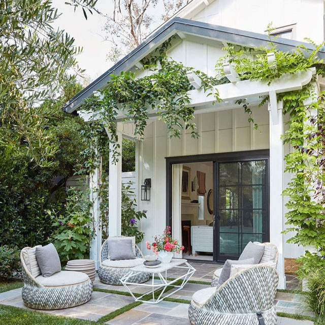 In this farmhouse-style Santa Monica home, designer Natasha Baradaran (@natashabaradaran) makes the combination of Bohemian and Art Deco work well together, with an emphasis on laid-back luxury. Just off the living room, a patio is furnished with @dedon_official outdoor lounge chairs and a cocktail table by Baradaran. Click the link in bio to take a look inside. Written by @bebehoworth, photography by @rogerdaviesphotography.