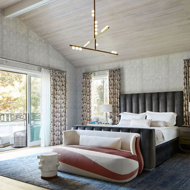 A Santa Monica farmhouse-style home designed by Natasha Baradaran (@natashabaradaran) is the perfect marriage of boho and Art Deco. The walls in the primary bedroom are sheathed in a hemp wallcovering by @phillipjeffriesltd; the custom tufted bed is dressed in linens by @leontinelinens; and a curvy settee by Baradaran nods to Deco but, with its swooping two-toned upholstery, feels lighthearted and fun. The stool is by @natanmoss, and the chandelier is by @lindseyadelman. Click the link in bio for the full tour. Written by @bebehoworth, photography by @rogerdaviesphotography.
