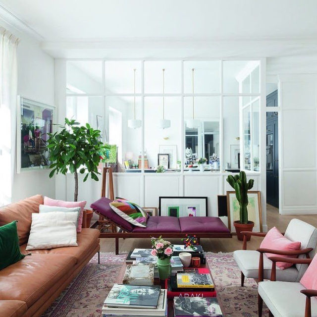 """As @sezane founder Morgane Sezalory (@morganesezalory) searched for an oasis in pink and green to call home, her dream came true when she discovered this 1,883-square-foot apartment in a beautiful 18th-century building in Paris, in the heart of Saint-Germain-des-Prés. The home, which was featured in @inesdelafressangeofficial's 2018 """"Maison: Parisian Chic at Home,"""" is straight out of a movie. In the living room, Sezalory knocked down the top half of a wall to create an expanse of glass, which opens up striking new perspectives and brings life and light to the interior. Click the link in our bio for the full story, which we've pulled from the ELLE Decor archive. Written by @moniquevaleris and photographed by @claire_cocano for Maison: Parisian Chic at Home (@flammarionlivres)."""
