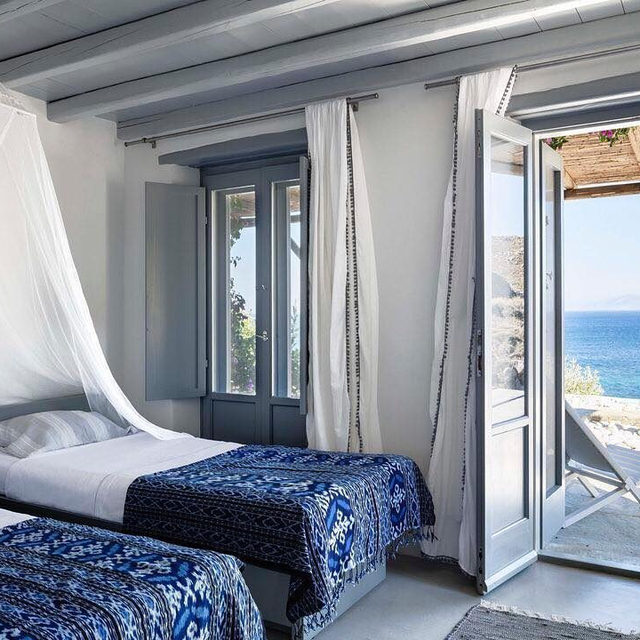 Like most traditional Greek dwellings, this home designed by Andrew Sheinman of Pembrooke & Ives (@pembrookeandives) is configured to draw guests outdoors. A series of sundecks and terraces fan out organically from the structure, leading out to views that overlook the Aegean Sea. In a guest bedroom, the blankets are by @andriannashamaris, and the curtains are of a custom fabric edged with pom-poms. Click the link in our bio for more. Written by @zabranowicz, produced by @mieketenhave, photographed by @ricardolabougle for ELLE Decor's July/August 2018 issue.