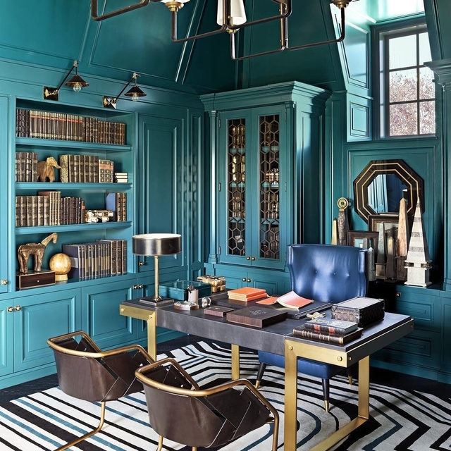 Working from home got you down? Get lost in the maximalist Beverly Hills manse of Too Faced founders @jerrodblandino and Jeremy Johnson, designed by Mary McDonald (@marymcdonaldinc). In Johnson's office, bold teal hues bring a new look to an old-world library. The desk chair is by @desousahughes, and the pair of @henge07 chairs is from @massbeverly. The 1960s desk lamp is by Jacques Adnet, the chandelier is by @luccaantiques, and the rug is a Mary McDonald for @pattersonflynnmartin design in Empire Stripe. Click the link in bio for the full tour, as seen in our March 2019 issue. Written by @vwlawrence, photographed by @douglasfriedman.