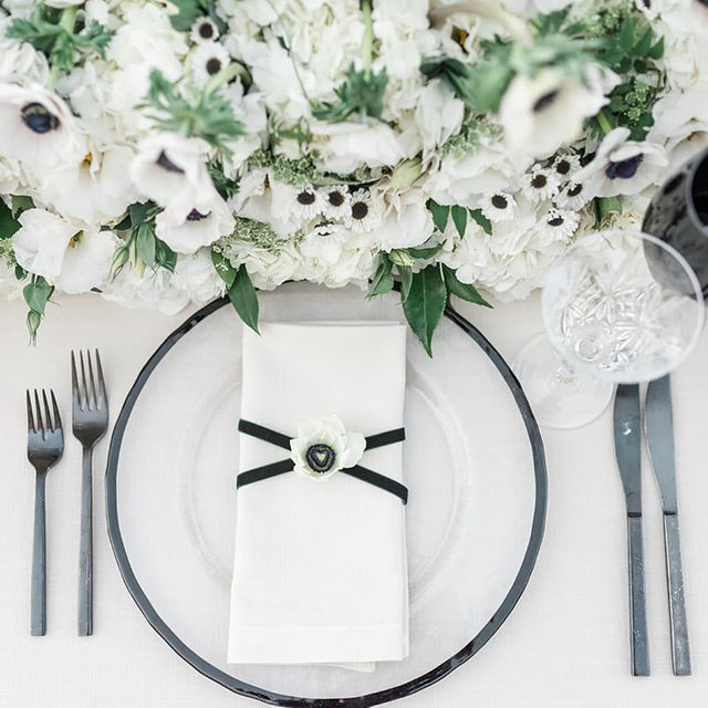 Holy chic! 🤍🖤 🤍 Timeless elegance, this classic white and black tablescape exquisitely demonstrates that less can truly be more. Featuring our Egret Sonoma Table Linen, Egret Sonoma Napkin & Hammered Clear with Black Charger. Visit the link in our bio to learn more about our featured products.  _________ Credits:  Planner: @angelicaroseevents Photographer: @cwardphotog  Floral: @girlluvsflowers @rootsflowerslv Rentals: @rsvppartyrentals Venue: @southernhighlandsgc