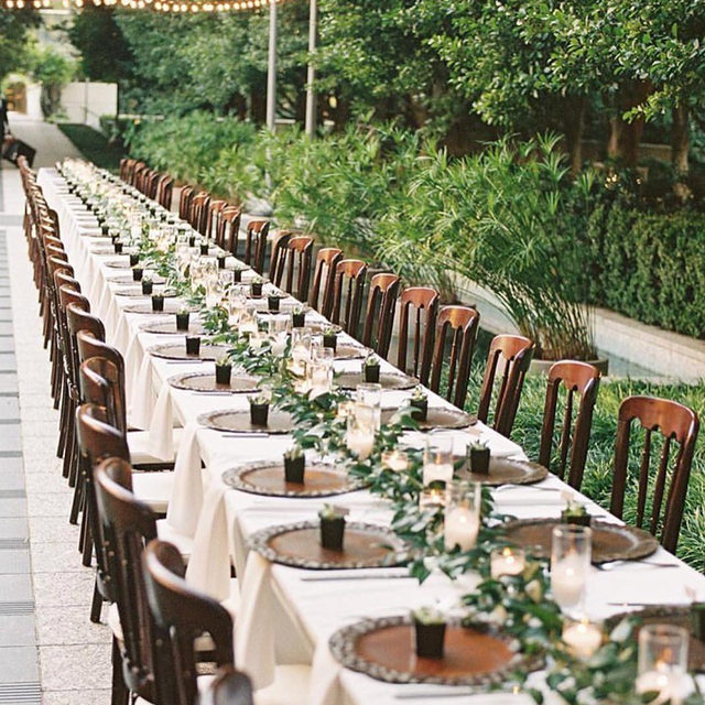 Find us under the garden lights. ✨ This sprawling reception table is banquet seating goals! Regardless of the length, this style of sitting instantly creates a cozy familial feel. Making for a romantic, intimate soiree with endless décor opportunities.  Featuring our White Classic Table Linen and White Classic Napkin. Visit the link in our bio to plan your next event! _________ Credits:  Planner: @gritandgoldeventco Photographer: @shannons_photo Floral: @ohdeeryfloral Venue: @mariegabrielle_
