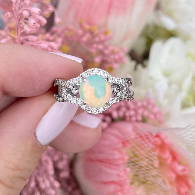 Obsessed with this round Opal set in 14K Vanilla Gold with a stunning twist shank setting encrusted with Chocolate and Nude Diamonds. ✨ This glistening solitaire ring is guaranteed to make a stylish statement with its remarkable color play. #LeVianColors  Link in bio to shop the piece exclusively at @jaredthegalleriaofjewelry