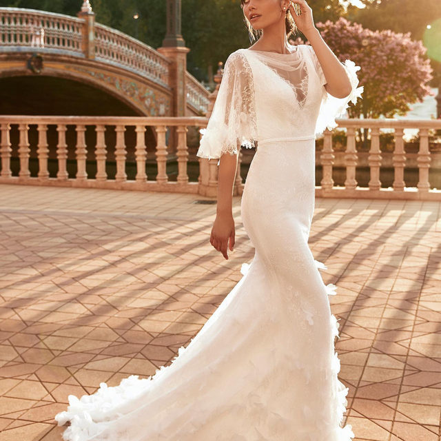 Gorgeously feminine with delicate lace sleeves and 3D flowers all over the train. In stores April 2021! Be the first to discover the #MarchesaForPronovias collection: book your appointment. (Dress: Roc)