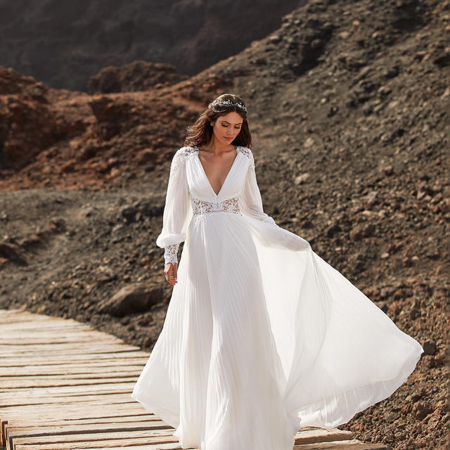 Do you dream of a wedding by the sea? The Bernadette dress has that boho touch while remaining sophisticated & glamorous! Book your appointment now. #Pronovias