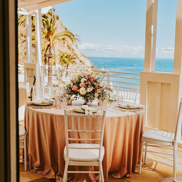 When the table is as beautiful as the view. 😍  With the ocean as your backdrop, it's hard not to get swept away in the beauty of it all. If anyone needs us, we'll be dreaming of dining seaside. Featuring our Cameo Velvet Table Linen, Boca Napkin, and Whitewash Wicker Placemat. Use the link in our bio to see more of these stylish products.  _________ Credits: Planner: @catalinaweddings Photography: @carrierogersphotography Rentals: @theperfectevent.inc, @bakerparty Venue: @visitcatalinaisland