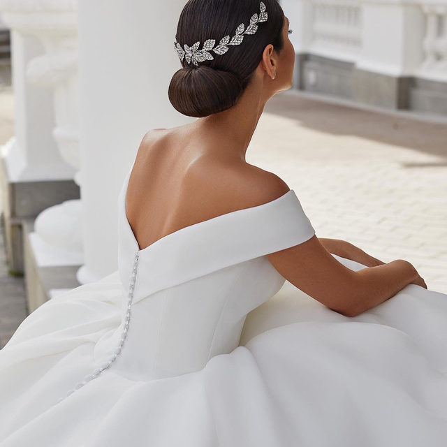 That off-the-shoulder bodice and V-shaped neckline of the Farrah gown. Discover the most beautifull ballroom style wedding gowns at your nearest #Pronovias. Link in bio to book your appointment.