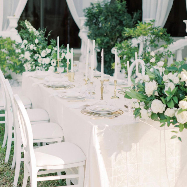 With all white florals, tons of green texture, and chic gold accents, we are absolutely infatuated with this oh-so-chic tablescape. 🤍 A timeless color scheme, white and green is the perfect combination for almost every wedding style. Featuring our Pearl Entangled Table Linen, Snow Crest Napkins, and Gold Edge Placemats. Use the link in our bio to see more of these gorgeous products.  _________ Credits: Planner: @mostlybecky Photography: @loveandcovenant Florals: @signatureflorals Rentals: @set_and_styled, @taylorrentalnaples Venue: @lacasatoscana